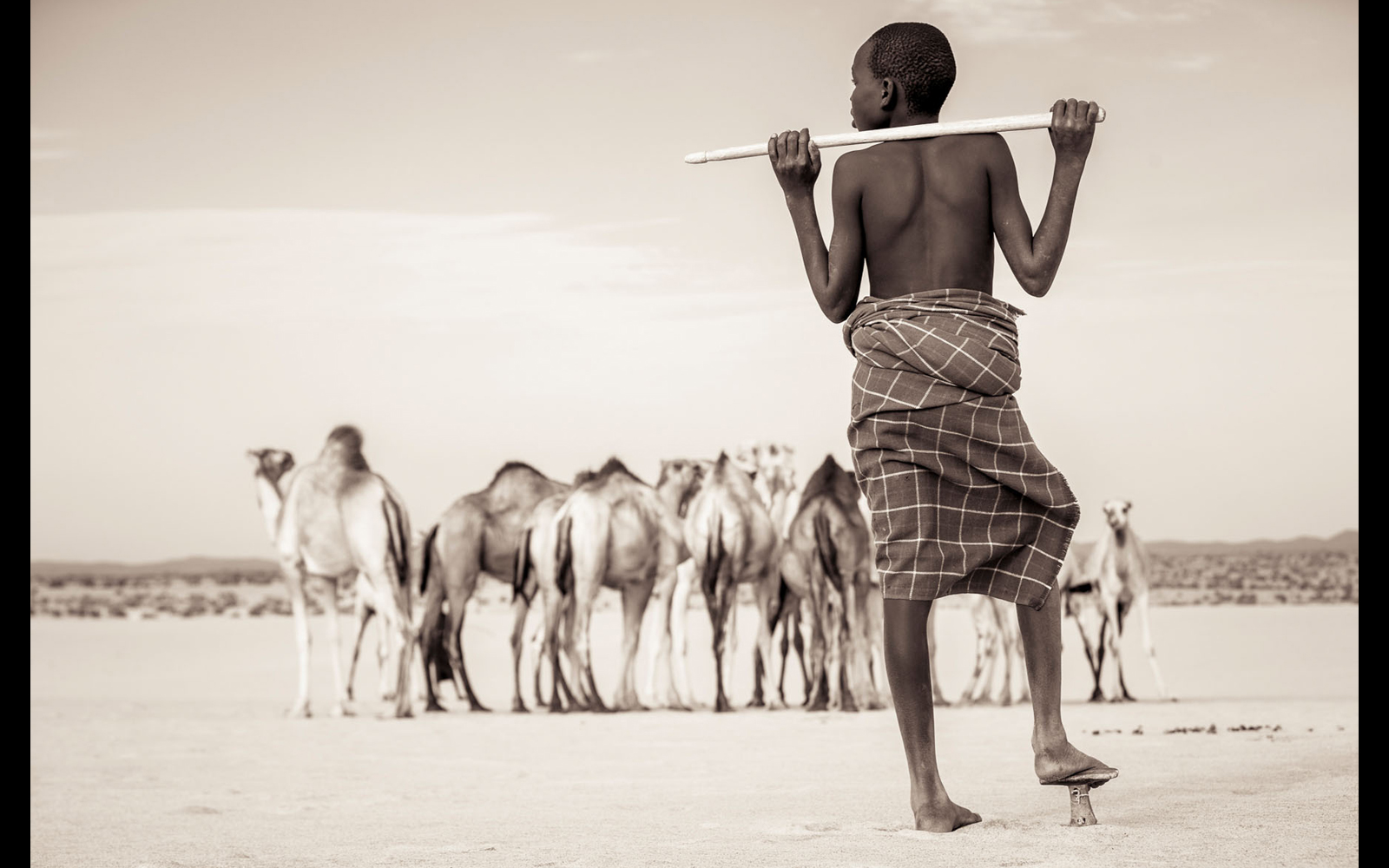 "A Turkana boy keeping an eye on his camels near a waterhole © <a href=""https://content.notesfromtheroad.ch/turkana-cradle-of-mankind/"" target=""_blank""> Joe Bürgi</a>"
