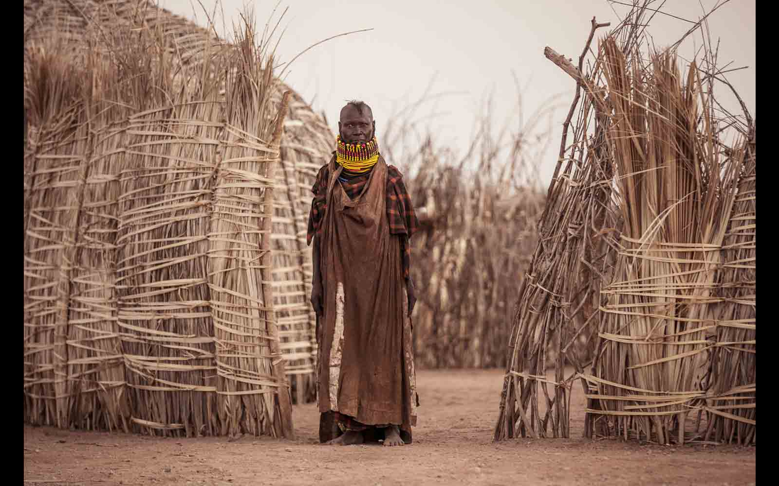 "Turkana tribeswoman outside her home – the huts and fences are constructed from doum palm leaves © <a href=""https://content.notesfromtheroad.ch/turkana-cradle-of-mankind/"" target=""_blank""> Joe Bürgi </a>"