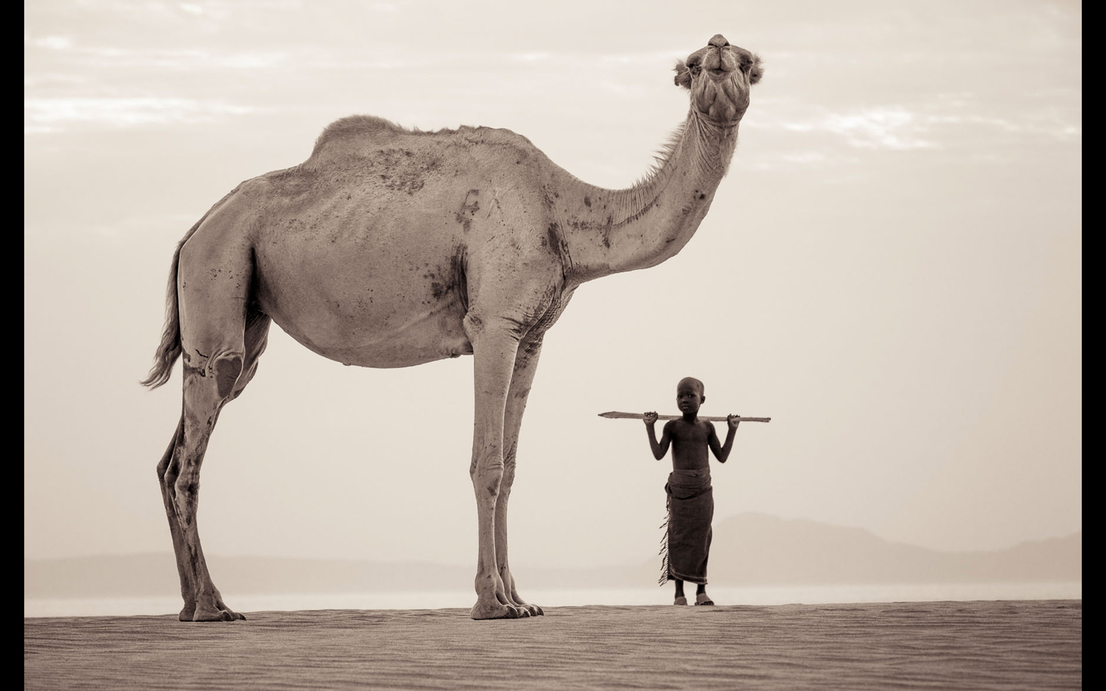 "A young herder and his camel on the dunes of Lake Turkana © <a href=""https://content.notesfromtheroad.ch/turkana-cradle-of-mankind/"" target=""_blank""> Joe Bürgi </a>"