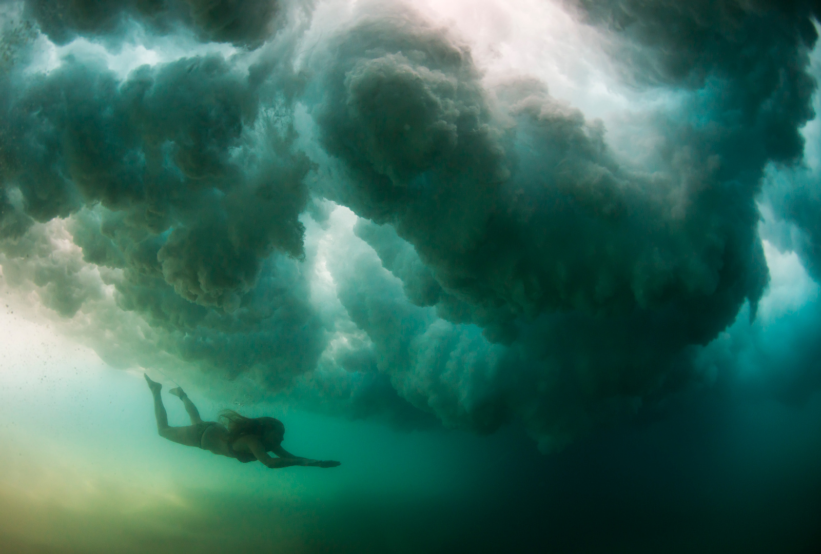 A swimmer dives underneath a breaking wave at Clansthal, South Africa ©Anthony Grote