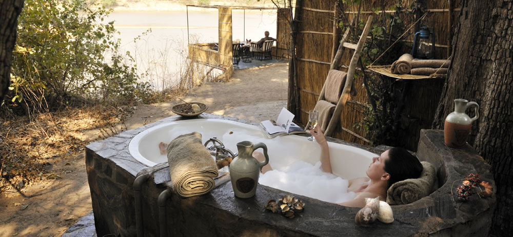 In addition to the indoor ensuite bathroom, each chalet has a stunning outdoor bathtub with shady views of a pod of hippos. A special feature of Kaingo are the unique individual decks built out over the river in front of each chalet.