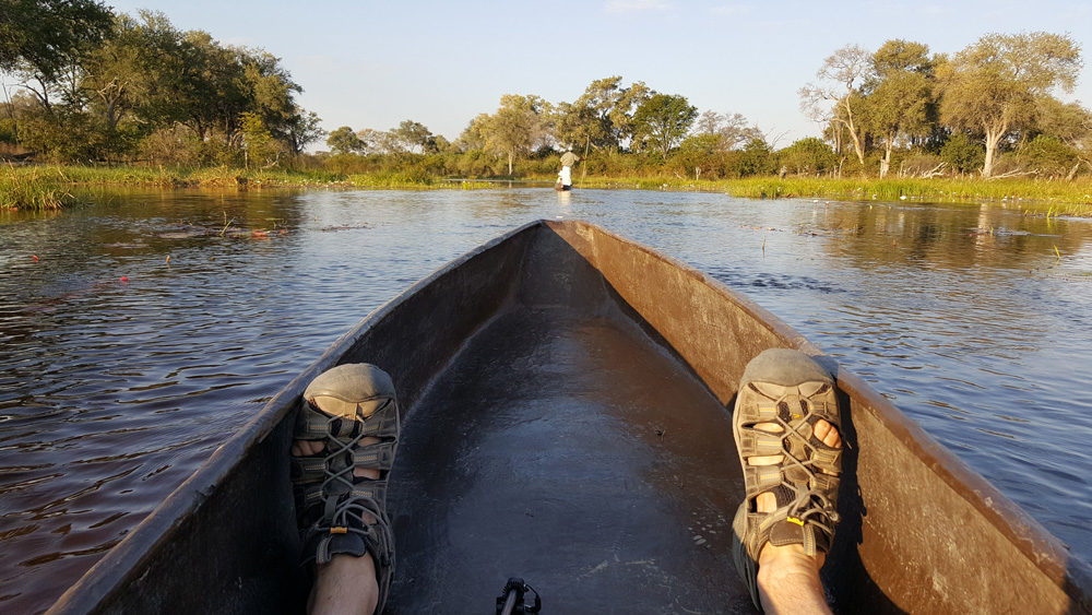 Feet in a mokoro while out on the waters of the Okavango Delta