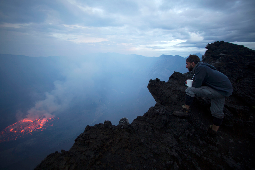 A man looking at down into the volcano crater
