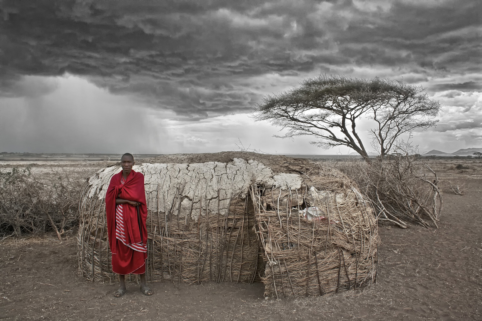 A proud Maasai warrior stands by his hut as a summer storm brews on the outskirts of the Serengeti National Park in Tanzania ©Andrew MacDonald