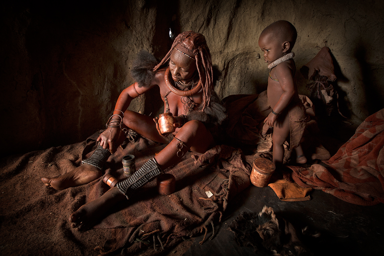 Each morning the Himba women in Otjimazeva Village, Namibia, undertake a lengthy beauty regime, whereby they crush small ochre stones into a fine powder before adding it to a butterfat mixture to apply to their bodies ©Ben McRae