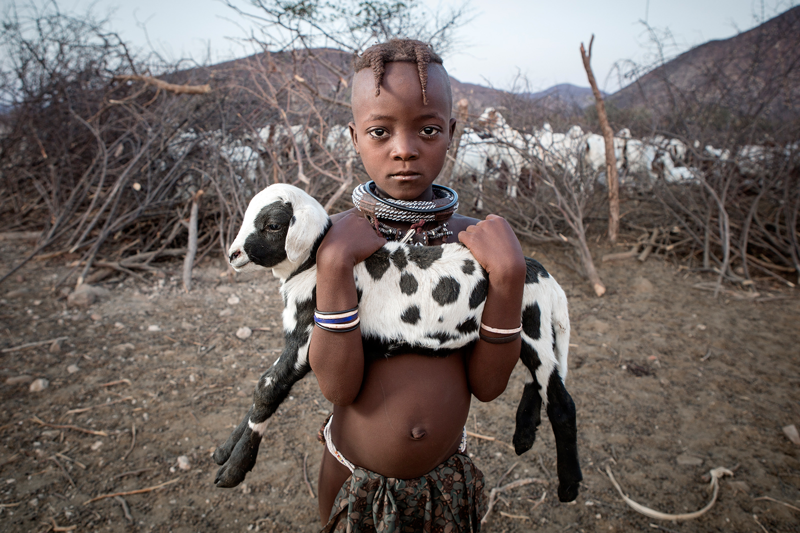 Keipepe holds her favourite goat in Otjimazeva Village, Namibia, after she has checked that all of the goats have made it through the night ©Ben McRae