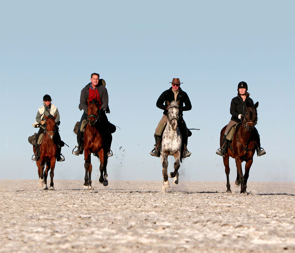 A group of people riding on horseback across the salt pans