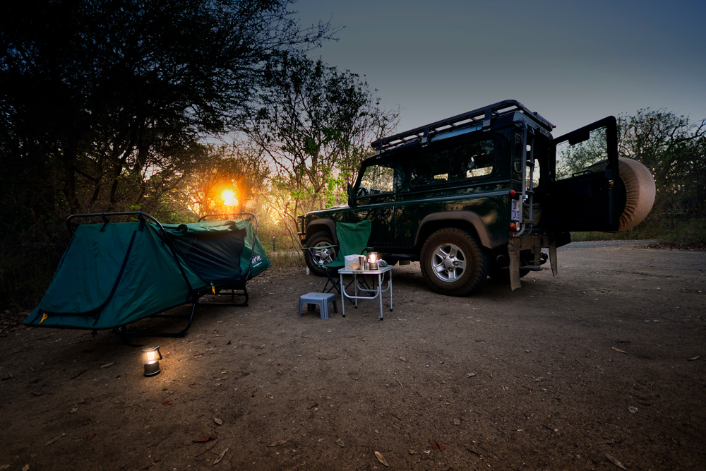 A tent-cot, camping table and 4x4 vehicle in Kruger National Park, South Africa