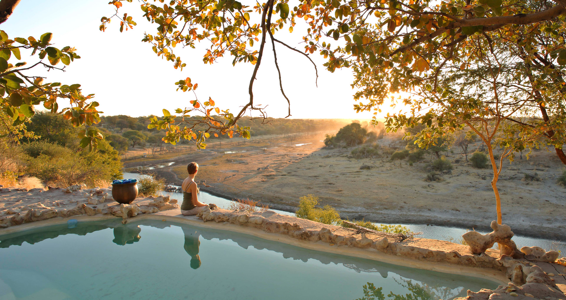 Person watching sunset from pool in Meno a Kwena, Botswana