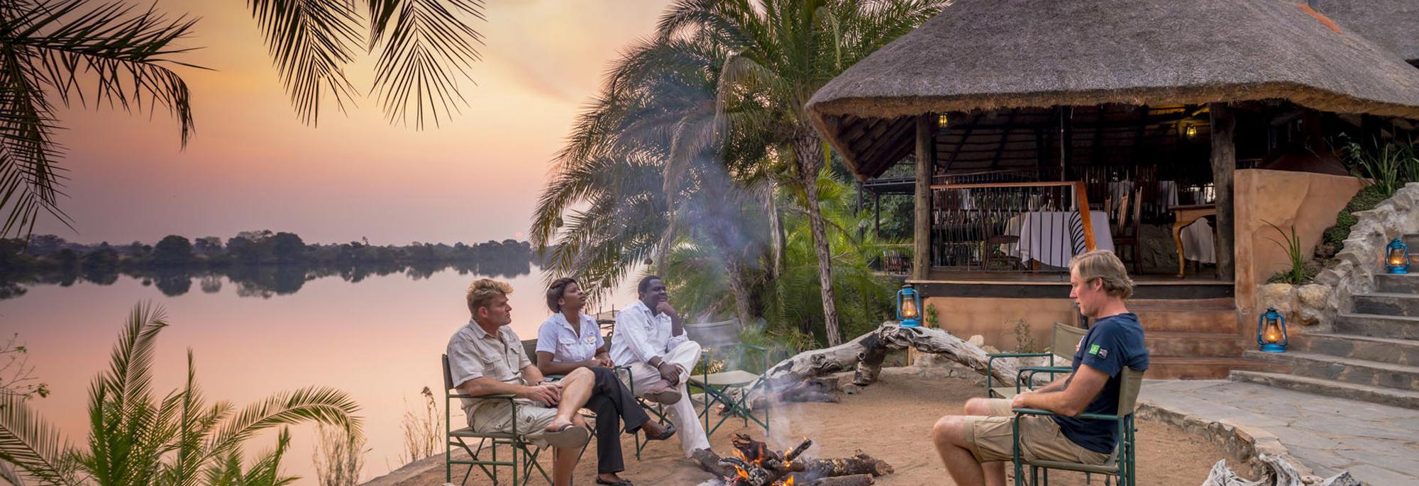 Guests around campfire at Mukambi Safari Lodge