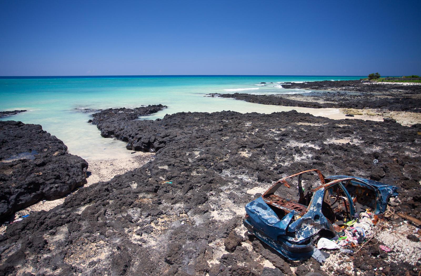 Abandoned car along the shoreline in Grande Comore