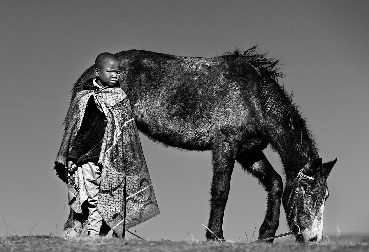 A boy holds onto his father's horse, awaiting their chance to compete in the King of Lesotho's horse race, near Semonkong, Lesotho © Hesté de Beer