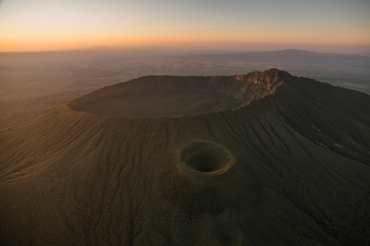 """Mount Longonot, a dormant stratovolcano, is green after a few weeks worth of rain. On the side of the main cone is a parasitic cone. These are formed when fractures exist along the side of the main cone. Eventually, those fractures reach the magma chamber and cause an eruption on the side of the main volcano and form what is called a parasitic cone. "" – Great Rift Valley, Kenya © Bobby Neptune"