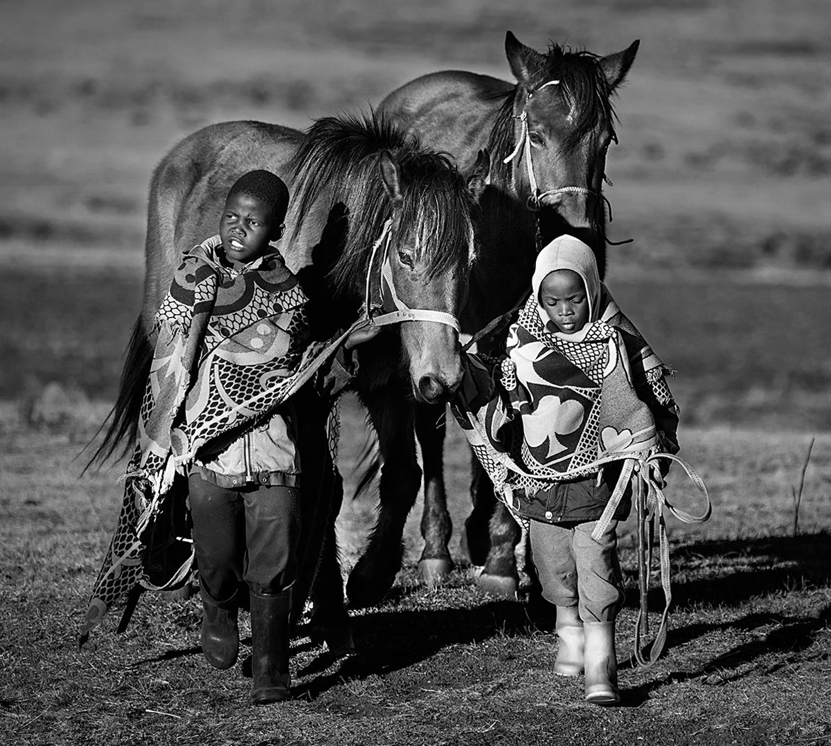 Two Basotho boys leading their horses toward the yearly King's horse race near Semonkong, Lesotho © Hesté de Beer