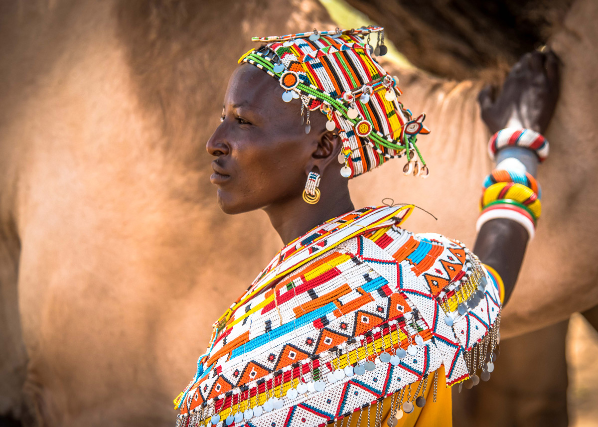 Mpayon, a Samburu woman who is one of nine Mama Tembos who patrol and help protect livestock and wildlife corridors, poses with a camel in Kalama, northern Kenya © Jane Wynyard