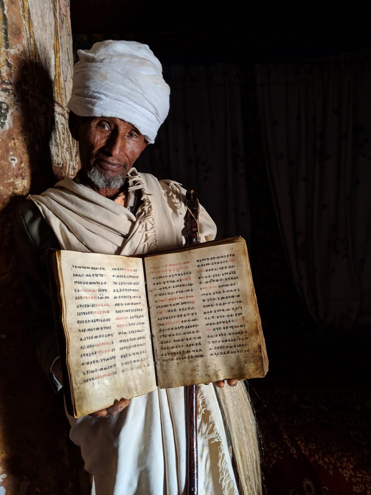 A priest holds the Bible in the Abuna Yemata Guh church, 2,580 metres above ground level. Its pages are made out of goat skin inked with Amharic letters, where the names of holy figures are written in red – Tigray Region, Ethiopia © Lukas Dennert