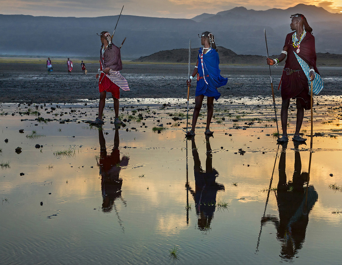 Maasai warriors watch on as the women approach the shores of Lake Natron in Tanzania © Hesté De Beer