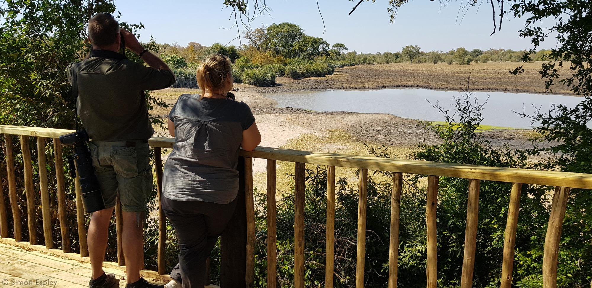 Two people viewing wildlife at Malugwe Pan, Zimbabwe