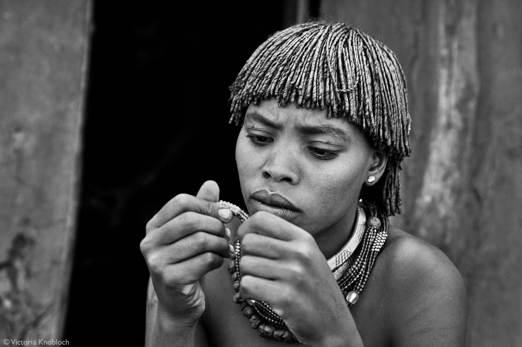 Hamer tribe woman beading, Omo Valley, Ethiopia