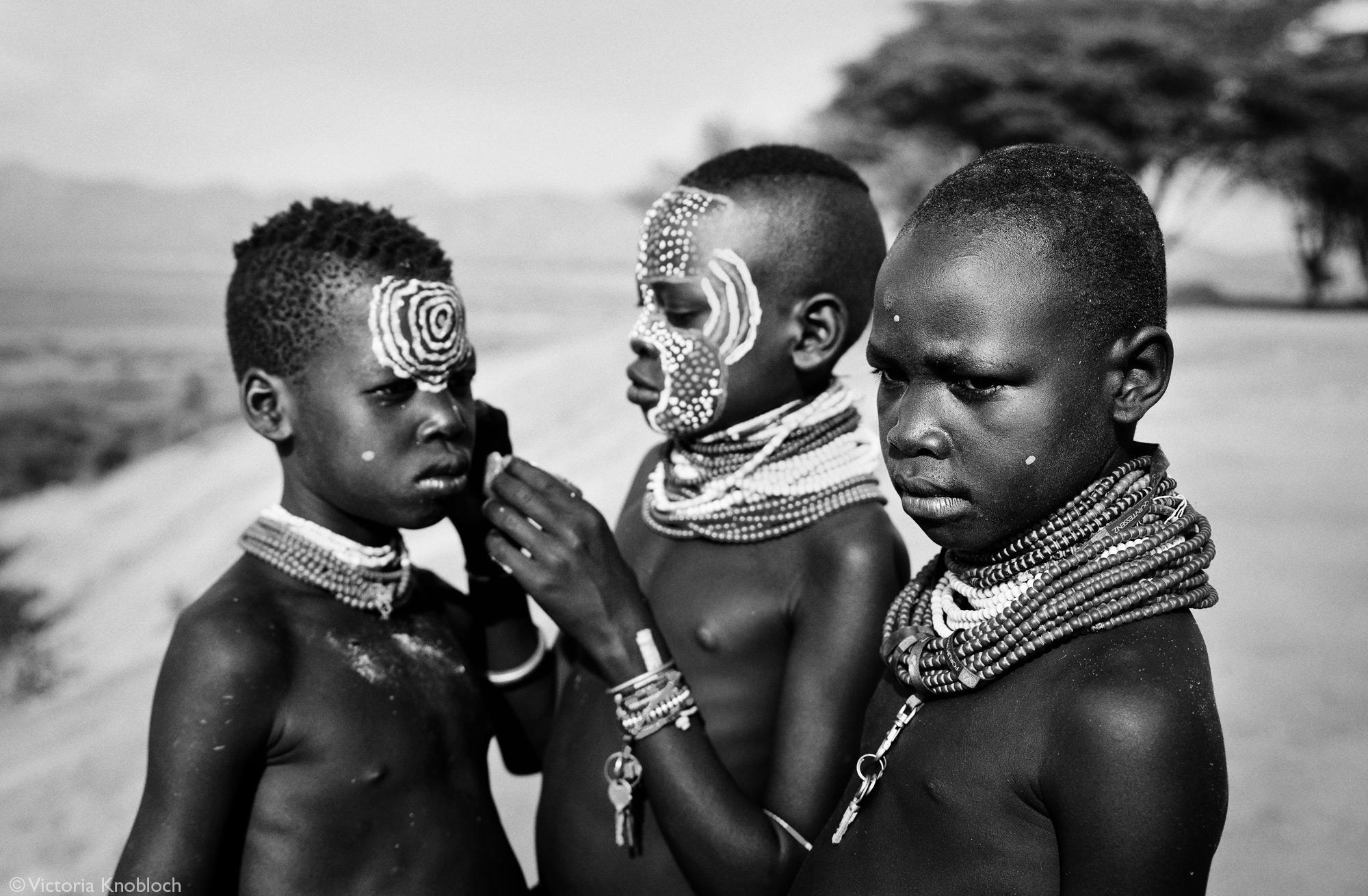 Karo tribe boys applying face paint, Omo Valley, Ethiopia