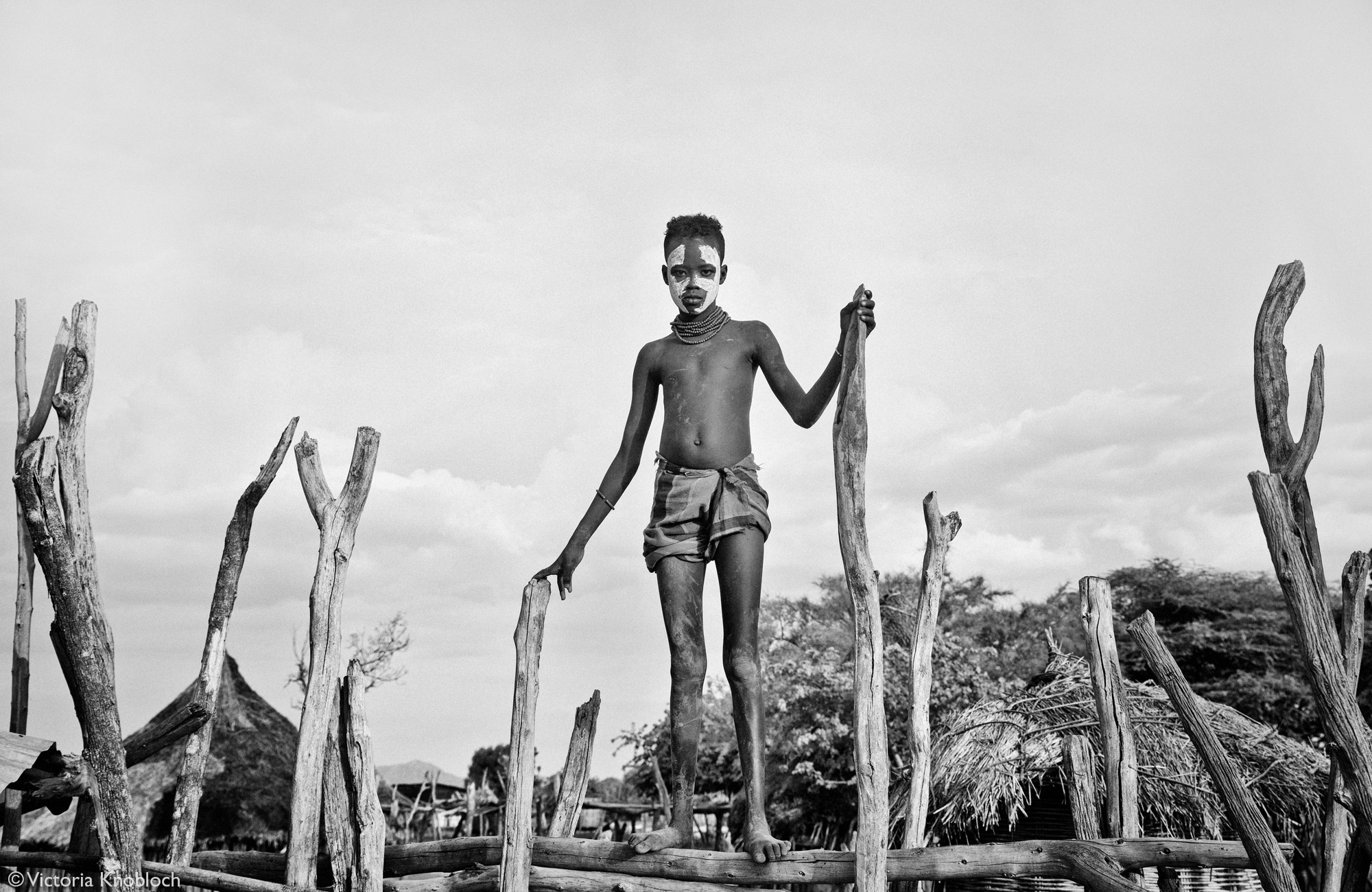 Karo tribe boy standing on top of wooden fence, Omo Valley, Ethiopia