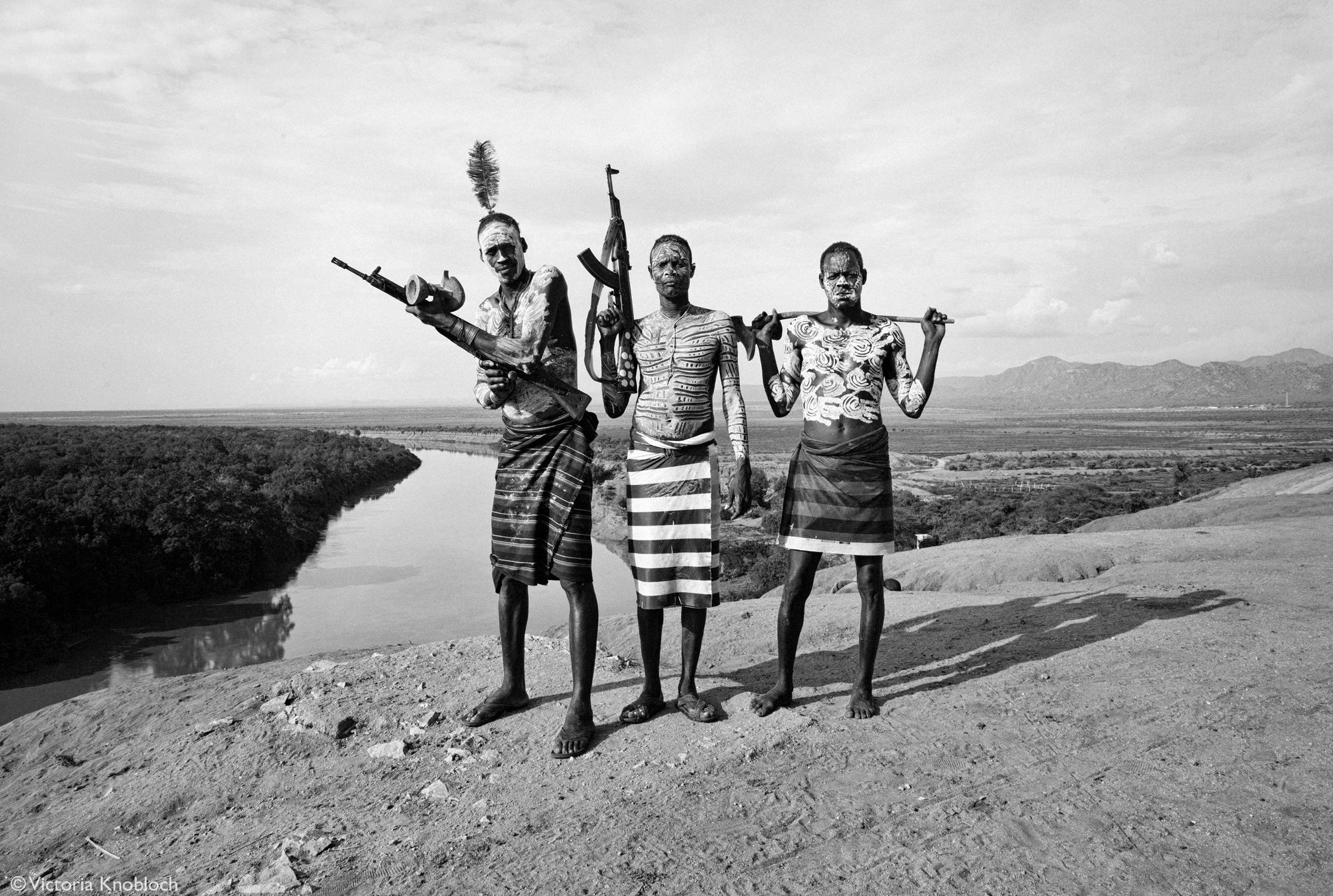 Men from the Karo tribe posing with their AK47s, Omo Valley, Ethiopia