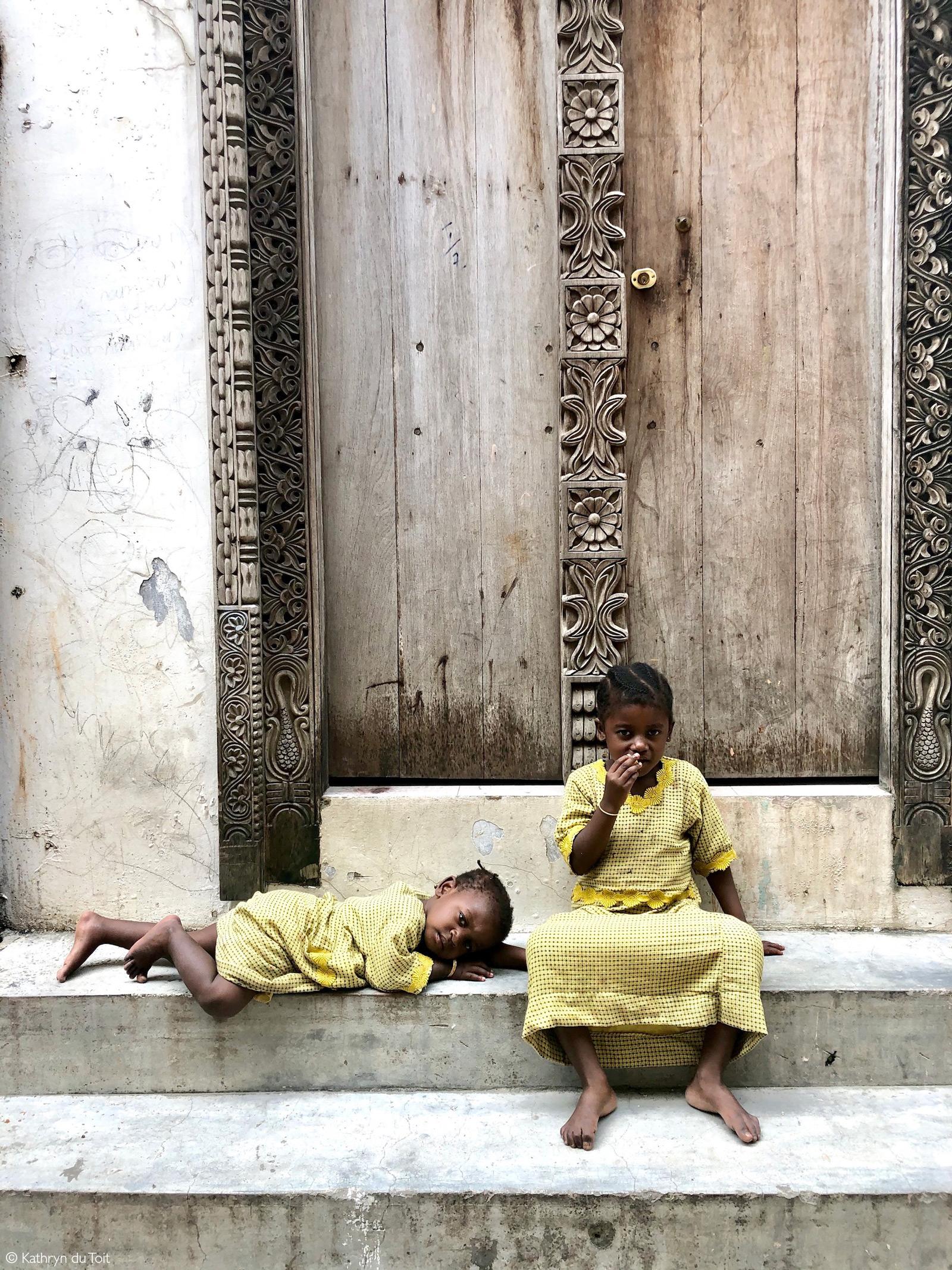 Children by a traditionally carved door. Stone Town, Zanzibar © Kathryn du Toit